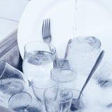 Glaswaren, Tischbesteck und Teller im Spülbecken Lizenzfreie Stockfotos