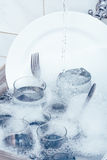 Glaswaren, Tischbesteck und Teller im Spülbecken Stockfotografie