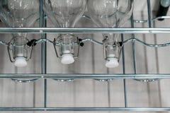 Glaswasserflaschen mit Weinlesekappe auf Metall beanspruchen stark stockfotografie