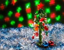 Glasweihnachtsbaum, der im funkelnden Lametta mit Weihnachtsdekorationen auf dunklem Hintergrund mit unscharfen Lichtern steht Stockfotografie
