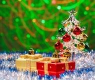 Glasweihnachtsbaum, der im funkelnden Lametta mit Weihnachtsdekorationen auf Hintergrund mit unscharfen Lichtern steht Lizenzfreie Stockfotografie