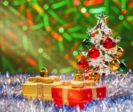 Glasweihnachtsbaum, der im funkelnden Lametta mit Weihnachtsdekorationen auf Hintergrund mit unscharfen Lichtern steht Lizenzfreies Stockbild