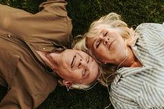 Glat äldre par som utomhus tycker om musik med leende arkivfoto