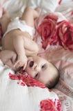Glat behandla som ett barn att ligga i säng på hans baksida royaltyfria bilder