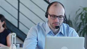 Glat call centermedel med hans hörlurar med mikrofon som talar se bärbara datorn lager videofilmer