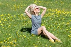 Glat flickasammanträde på gräset Arkivbilder