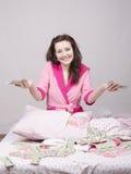 Glat flickasammanträde på säng med en packe av pengar Royaltyfri Bild
