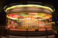 Glat går rundan, karusell, i rörelse på natten Arkivbild