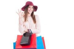 Glat nätt kvinnligt visningoktecken och bärande shoppingpåsar Arkivbild