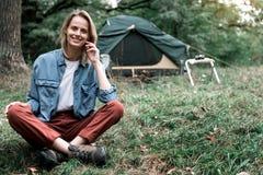 Glat sammanträde för ung kvinna på gräs i naturen arkivbilder