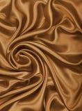 Glatte elegante goldene Seiden- oder Satinbeschaffenheit als abstraktes backgrou Lizenzfreie Stockfotos