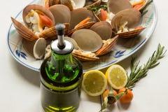 Glatte Muschel, Olivenöl in einer Flasche, Rosmarin und geschnittene Zitrone Lizenzfreie Stockbilder