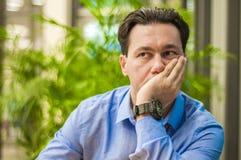 Glauben ermüdet Frustrierter junger gutaussehender Mann, der beim Sitzen seinem Arbeitsplatz erschöpft betrachtet Stockfotografie
