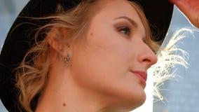 Glauben junge attraktive L?chelnfrau des Portr?ts im Hut und schwarzer Mantelblick auf Kamera im Stadtzentrum gl?cklichem Modem?d stock video footage