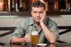 Glauben niedergedrückt. Porträt von den deprimierten jungen Männern, die Bier trinken Stockfotos
