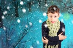 Glaubende Kälte des kleinen Jungen unter Schnee Stockfotos