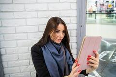 Glaubender Schock der Frau, wenn der Tabletten-PC verwendet wird stockbild
