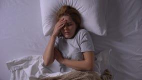 Glaubendes Fieber und Schmerz der jungen Frau in den Knochen, in fangendem Virus und im Lügen im Bett stock footage
