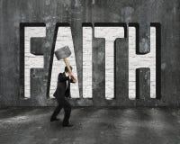 Glaubenwort auf Betonmauer mit dem Mann, der Hammer hält Lizenzfreie Stockbilder
