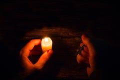 Glaubt Mann mit einer Kerze und einem Kreuz Lizenzfreies Stockbild