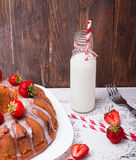 Glaze cake with strawberry and bottle with milk Royalty Free Stock Photo