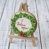 A glaze Christmas gingerbread cookie in the form of a Christmas wreath with a red bow and golden stars with inscription in Russian. Happy New Year - on a royalty free stock photo