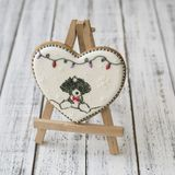 A glaze Christmas gingerbread cookie in the shape of a heart with a cute puppy and New Year`s garland on a white wooden table. royalty free stock photo