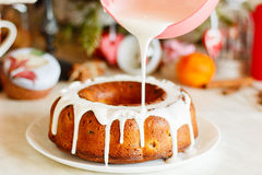 Glazed bundt cake with white glaze on Christmas background Royalty Free Stock Photography