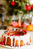 Glazed bundt cake with white glaze on Christmas background Stock Images