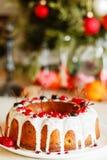Glazed bundt cake with white glaze on Christmas background Stock Images