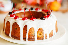 Glazed bundt cake with white glaze on Christmas background Stock Image