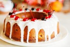 Glazed bundt cake with white glaze on Christmas background Stock Image