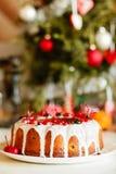 Glazed bundt cake with white glaze on Christmas background Royalty Free Stock Images