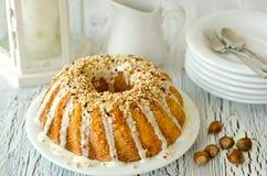 Glazed cake with hazelnuts on white background Stock Image