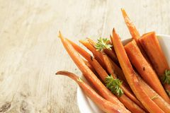 Glazed carrot sticks with parsley garnish in a bowl on a rustic. Wooden table, corner background with copy space, selected focus, narrow depth of field stock photos