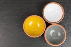 Glazed ceramic bowls. Three glazed ceramic bowls on black slate plate stock photo