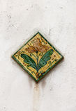 Glazed ceramic tile, with a flower and leaves Royalty Free Stock Photos