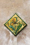 Glazed ceramic tile, with a flower and leaves Royalty Free Stock Photo