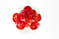 Glazed cherries with white back ground. Glazed cherries in a glass with some ice Royalty Free Stock Photo
