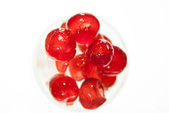 Glazed cherries with white back ground. Glazed cherries in a glass with some ice Royalty Free Stock Image