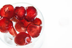 Glazed cherries with white back ground. Glazed cherries in a glass with some ice royalty free stock photography
