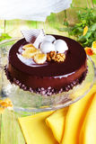Glazed chocolate cake with banana and walnuts, whole, still life, close-up of a beautiful, spring, food, atmosphere, decor, pansie Royalty Free Stock Image