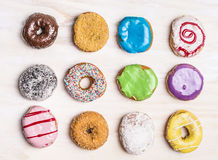 Glazed colorful doughnuts with sprinkles and icing on white wooden background, top view. Glazed colorful doughnuts with sprinkles and icing white wooden royalty free stock photos