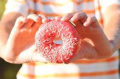 Glazed donut closeup. Child holding tasty glazed donut closeup, selective focus Stock Photography