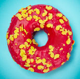 Glazed donut with colorful sprinkles on blue pastel background. Royalty Free Stock Image