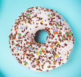 Glazed donut with colorful sprinkles on blue pastel background. Stock Photos