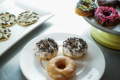 Glazed donuts and cookies on plates royalty free stock image