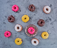 Glazed Doughnuts with colourful sprinkles on dark background Royalty Free Stock Images