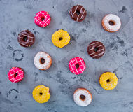 Glazed Doughnuts with colourful sprinkles and icing on dark background Stock Images