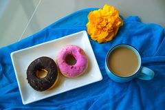 Glazed doughnuts with sugar and chocolate sprinkles and a cup of coffee. stock photography